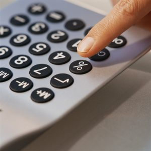 Finger Pressing Button on Calculator --- Image by © Royalty-Free/Corbis