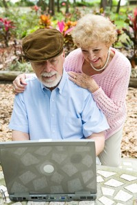 Happy senior couple using their laptop computer outdoors. Focus on husband.