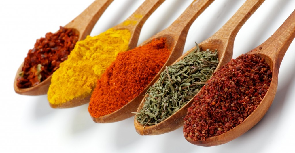 Arrangement of Spicy Spices with Ground Sumach, Oregano, Dried Paprika, Curry and Crushed Chili in Wooden Spoons isolated on white background